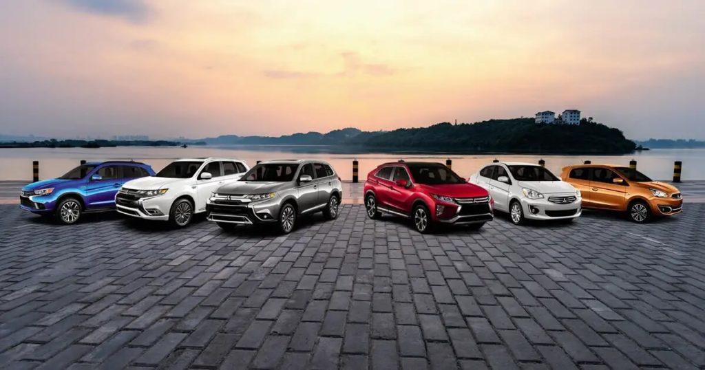 La gamme de six véhicules Mitsubishi garés sur un quai au bord d'un fleuve
