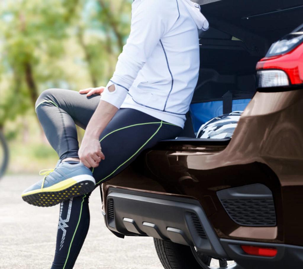 Femme ajustant ses souliers de jogging assise sur le bord du coffre du Mitsubishi RVR 2021