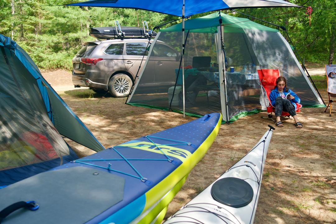 vue latérale du Mitsubishi Outlander PHEV 2022 derrière une tente