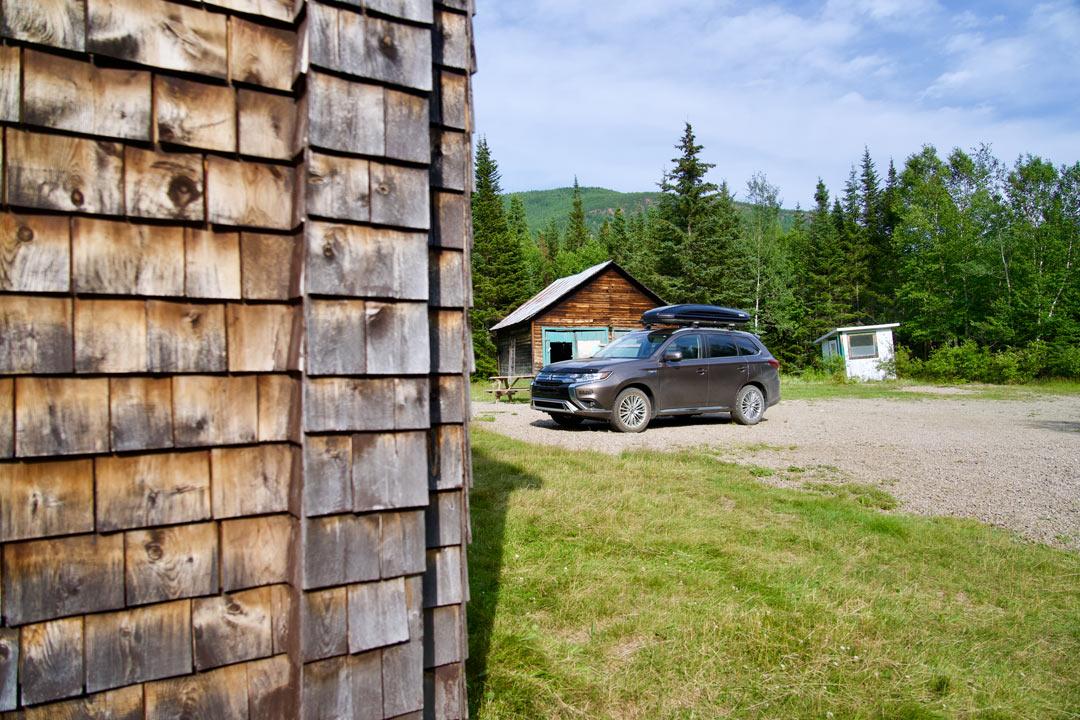 vue latérale du Mitsubishi Outlander PHEV 2022 stationné devant une cabane